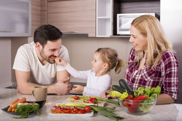 キッチンで野菜と新鮮なサラダを作る小さな娘と幸せな家族