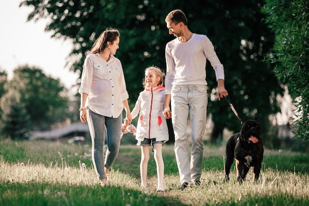 Happy family with their pet for a walk in the park.
