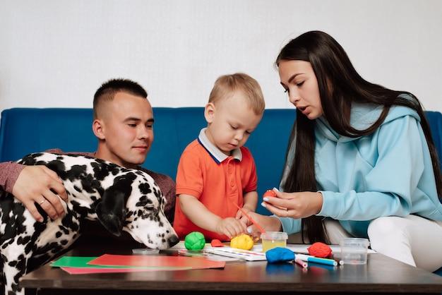 그들의 아들과 강아지 달마 시안과 함께 행복한 가족은 집에서 테이블에 앉아 플라스틱으로 페인트하고 조각합니다.