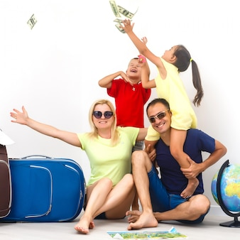 A happy family with their suitcases on a white