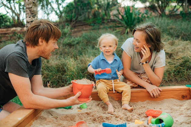 Happy family with toddler child playing in sandbox