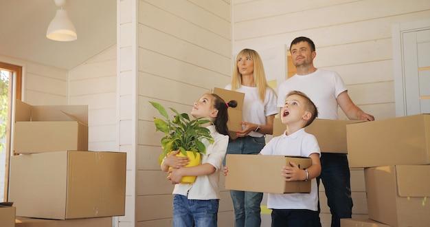 Счастливая семья с двумя детьми в новом доме держит коробки