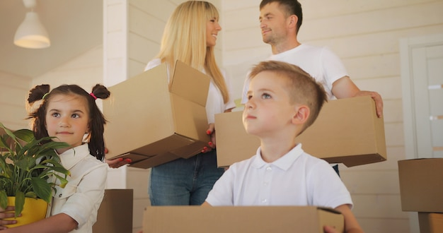 Счастливая семья с двумя детьми в новом доме. мать отец и ребенок в новом доме