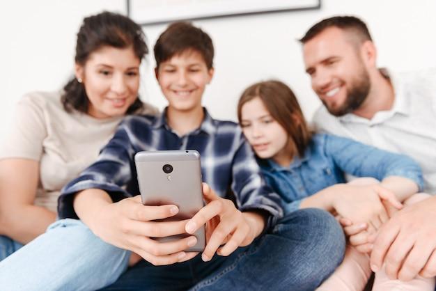 Счастливая семья с двумя детьми сидит на диване вместе дома и делает селфи на мобильном телефоне