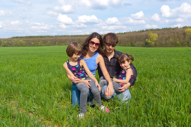 Happy family with two kids on green field