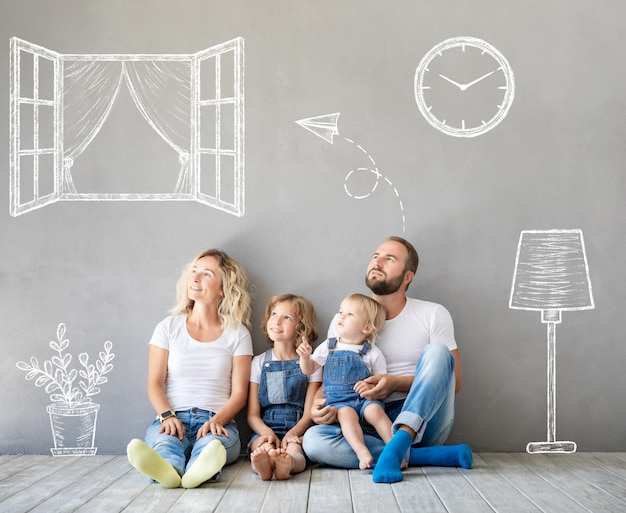 Happy family with two kids playing into new home