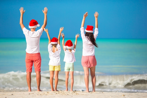 Happy family with two kids in santa hat on summer vacation