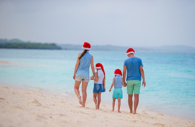 Happy family with two kids in santa hats on summer vacation