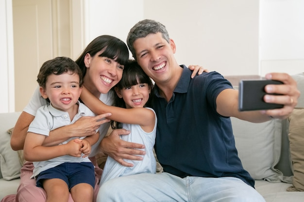 Happy family with two little kids sitting on couch at home together, taking selfie