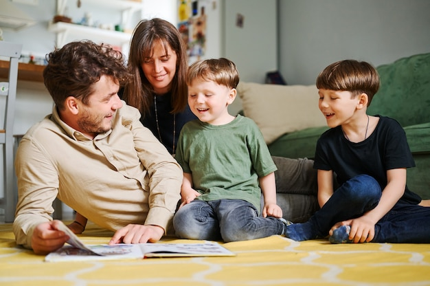 Счастливая семья с двумя маленькими сыновьями, читающими рассказ в помещении, родители с детьми проводят время вместе и лежат на полу дома