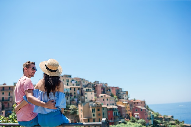 Happy family with view of the old coastal town of vernazza, cinque terre national park, liguria, italy
