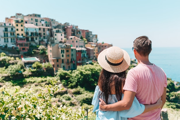 Happy family with view of the old european village in cinque terre national park, liguria, italy