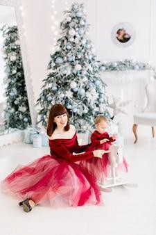 행복 한 가족, 여자 어머니와 어린 소녀 크리스마스 트리 근처 재생