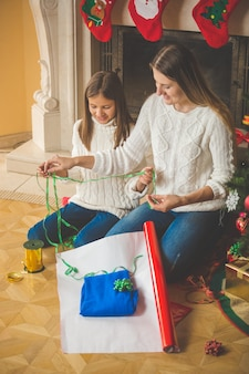 暖炉でクリスマスプレゼントを包む幸せな家族