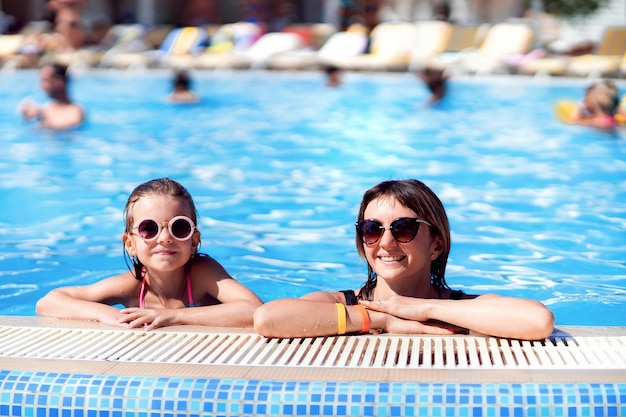Happy family, young active mother and adorable little daughter having fun in a swimming pool enjoying summer vacation at a tropical resort