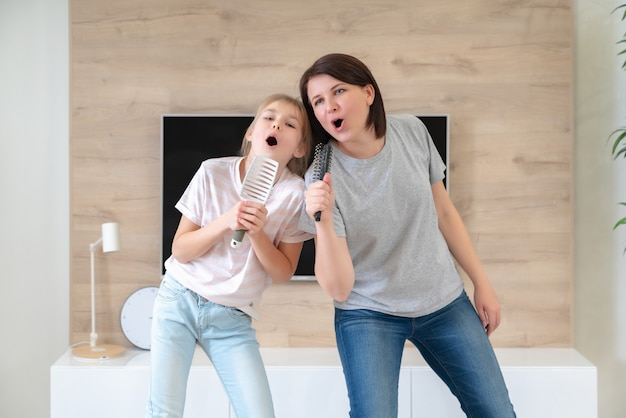 Happy family young adult mother and cute teen daughter having fun singing karaoke song in hairbrushes. mother laughing enjoying funny lifestyle activity with teenage girl at home together.