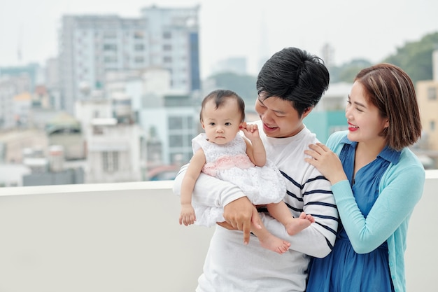 Happy family of young asian father, mother and little daughter standing on balcony of their apartment