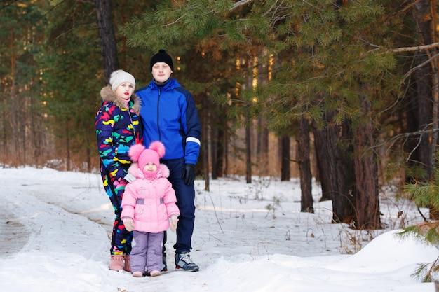 Счастливая семья, молодая пара и их дочь проводят время на открытом воздухе зимой