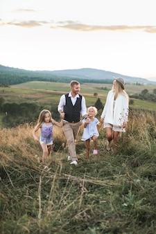 幸せな家族、若い父親、フィールドを歩いて彼の小さな娘を持つ母