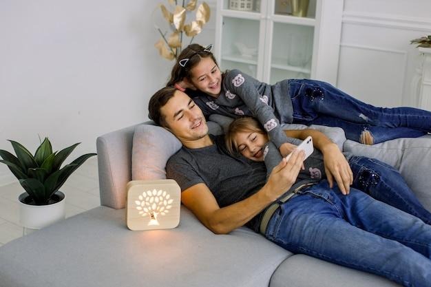 Счастливая семья, молодой человек со своими двумя маленькими сестрами, весело проводящий время в уютной современной гостиной, лежа на сером диване с деревянной ночной лампой ручной работы.