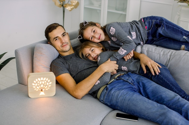 Happy family, young man with his two little sisters, having fun at cozy modern living room, lying on gray sofa with wooden hand made night lamp.
