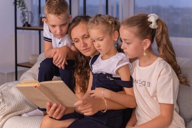 小さな子供たちに座っている面白いおとぎ話を伝える本を読んで幸せな家族の若いお母さん乳母