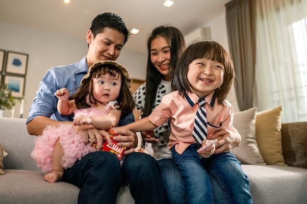 幸せな家族子供たちは、リビングルームのソファで両親の膝の上に座っています子供たち