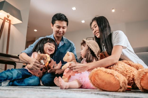 幸せな家族親は子供たちが敷物の上に座ってテディベアやおもちゃで遊ぶ