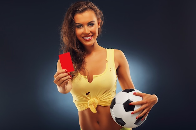 A happy fan holding football and showing red card