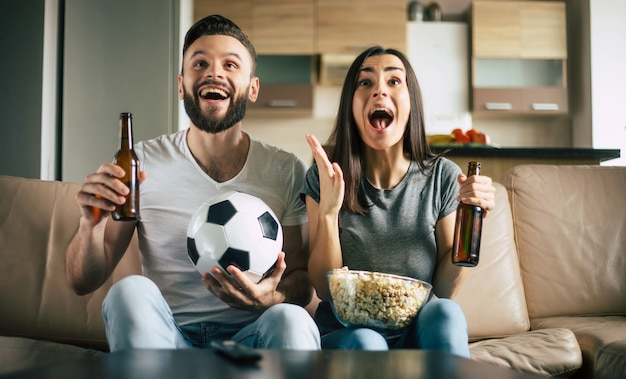 Счастливая пара болельщиков смотрит футбольный матч по телевизору с закусками, пивом и мячом на диване