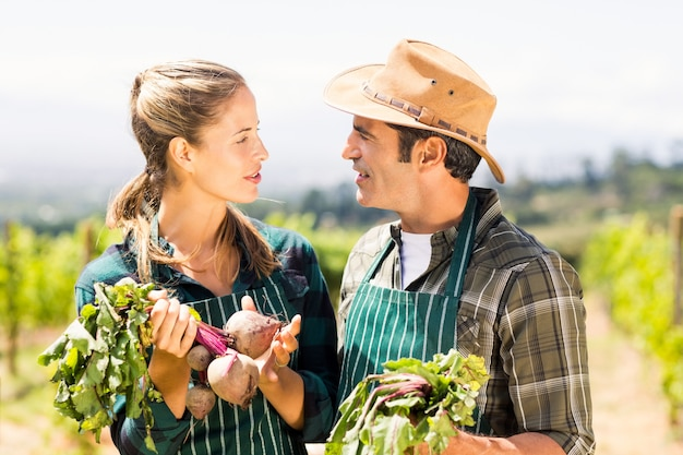 Happy farmer couple holding leafy vegetables
