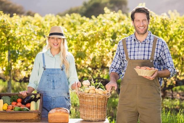 Счастливая пара фермеров, представляющих свои местные продукты питания