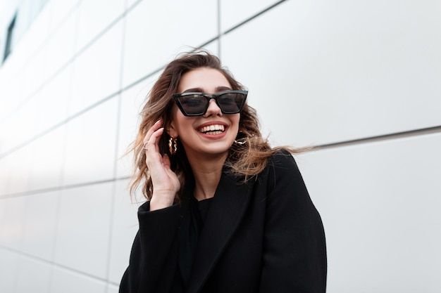 Счастливая модная девушка в стильной черной одежде