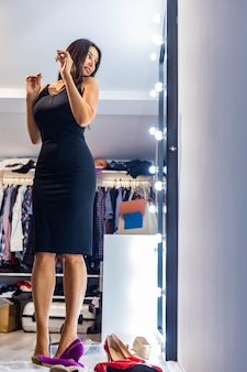 Happy fashion woman choosing outfit for party event looking at lighting mirror in dressing room