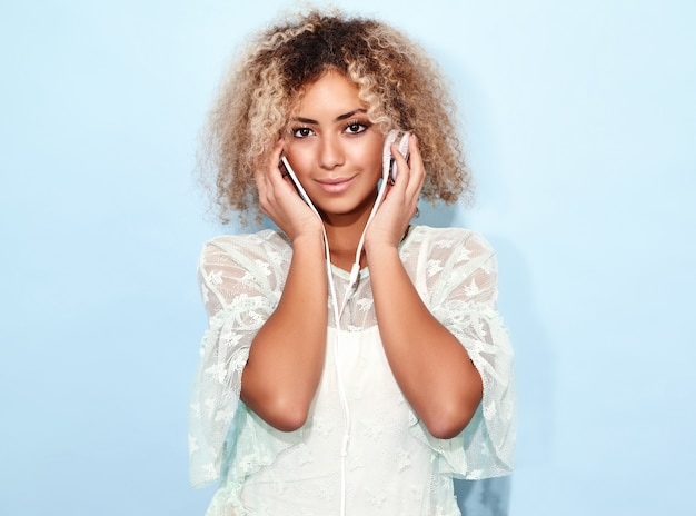 Happy fashion woman with blond afro hairstyle smiling and listening to music in headphones