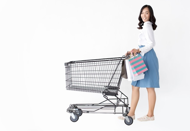 Happy fashionable asian girl with shopping bag on white isolate wall in red theme