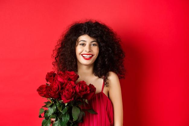 赤いバラの花束、笑顔とカメラ、スタジオの背景で陽気に見える幸せなファッショナブルな女性モデル。