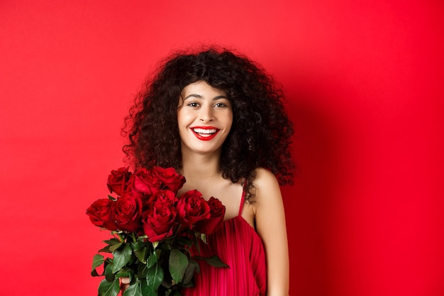 Happy fashionable female model with bouquet of red roses, smiling and looking cheerful at camera, studio background.