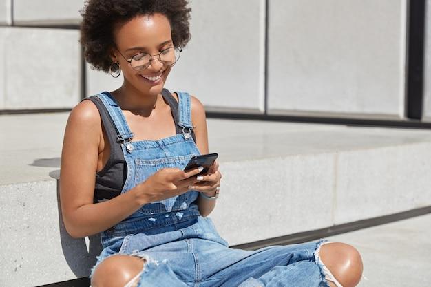 Felice blogger femminile alla moda siede a gambe incrociate all'esterno, invia messaggi di testo per post sul sito web personale, è di buon umore, invia feedback, indossa abiti eleganti per i giovani, gode del tempo libero
