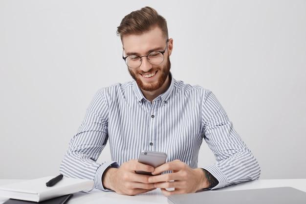 幸せなファッショナブルな男子学生が職場に座って、クラスの準備、携帯電話を保持