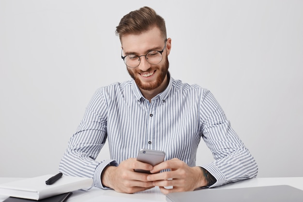 Happy fashionable male student sits on work place, prepares for classes, holds mobile phone