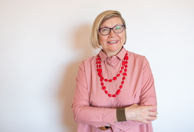 Happy fashionable senior woman gray hair senior woman, middle aged maturesmiling old woman wearing beads on a light background, positive lonely pensioner senior woman