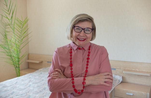 Счастливая модная старшая женщина седые волосы старшая женщина, улыбающаяся старуха средних лет в бусах на светлом фоне, позитивная одинокая пенсионерка старшая женщина