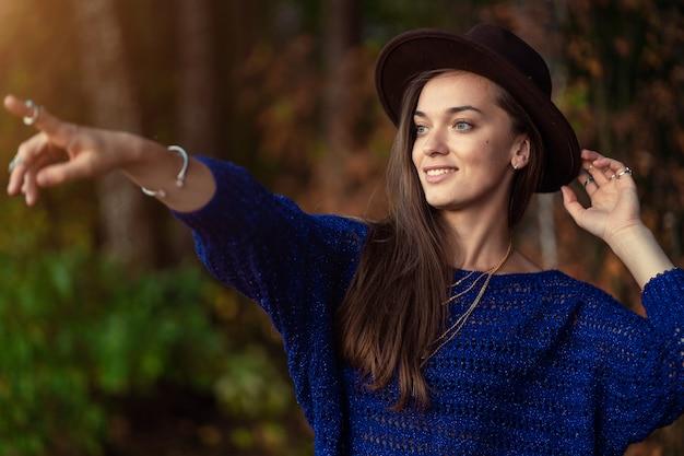 帽子とニットの青いセーターで幸せなファッショナブルなスタイリッシュな自由ho放に生きるシックな女性は、秋の森の距離に表示されます。