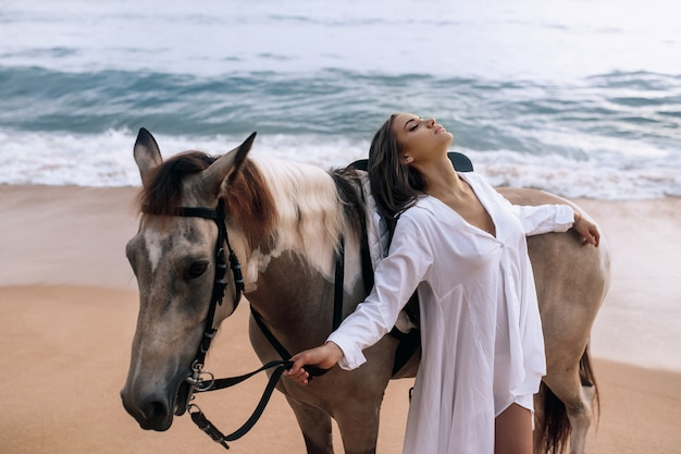 Happy fashionable young woman in a white dress posing with a horse on the beach.