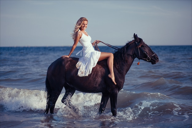 Happy fashionable young woman in white dress posing with a horse on the ocean beach