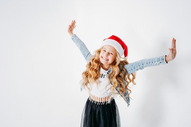 サンタ帽子、デニムジャケット、白地に黒のチュチュスカートで幸せなおしゃれな服装の巻き毛のトゥイーンの女の子