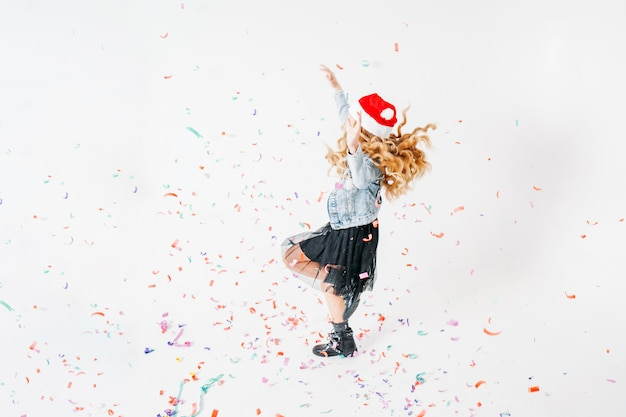 Happy fashionably dressed curly hair tween girl in santa hat, denim jacket and black tutu skirt on white  with colorful confetti