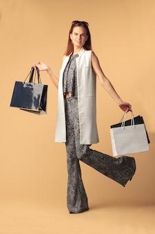 Счастливая модница с сумками, изолированными на бежевом фоне