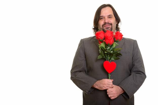 バレンタインデーの準備ができて赤いバラと心を持って笑っている幸せな太った白人ビジネスマン